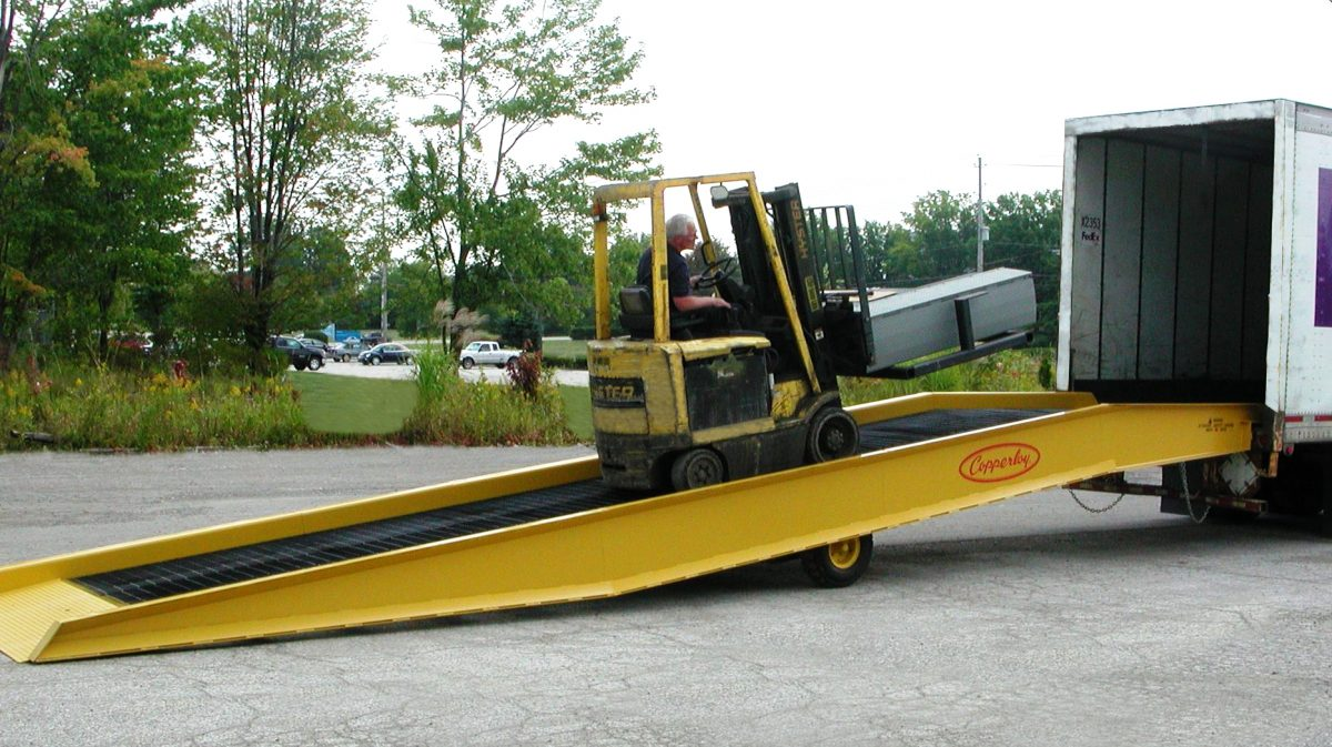 A forklift using one of Copperloy's hydraulic forklift ramps.