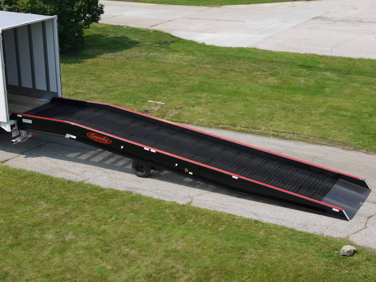 A Copperloy portable yard ramp connected to the back of a truck.