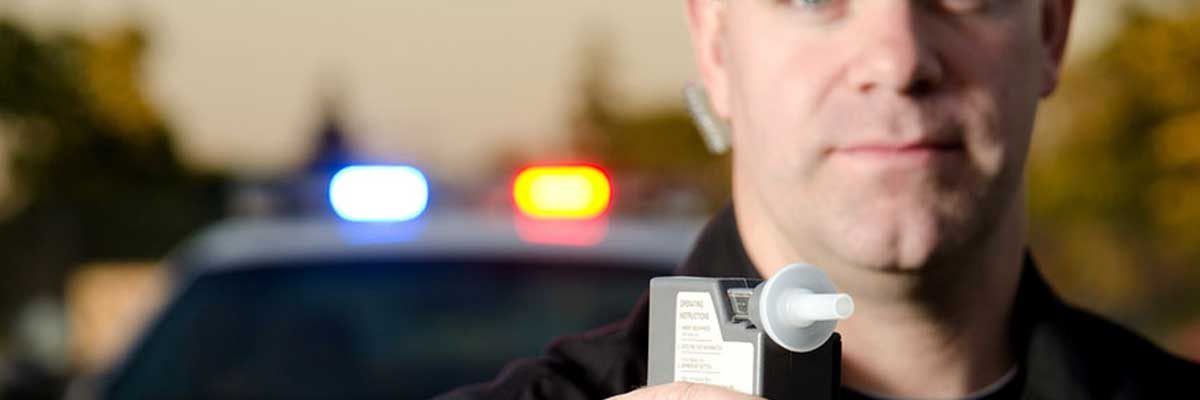 An officer with a breathalyzer. OVI / DUI lawyer Wadsworth Ohio.